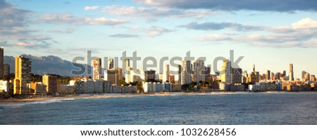 sunny sandy beaches of Benidorm with modern housing and mountains on background
