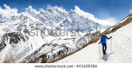 Sunny slope covered with snow and woman climbing with trekking poles. Outdoor among mountain peaks concept - stock photo