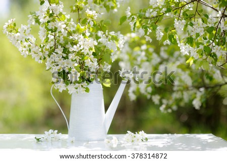 Sunny spring in the blossoming apple orchard. Bouquet of white flowers stands on a table