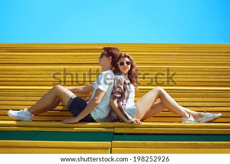 Sunny summer colorful photo stylish young cool couple teens rest on the bench in city park, blue sky - stock photo