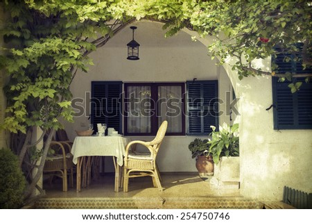 Sunny terrace with chairs and a lot o flowers - vintage photo - stock photo