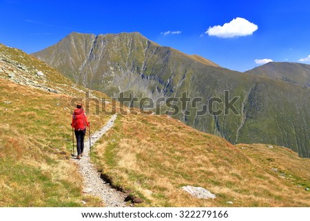 Sunny trail and isolated mountaineer with a red backpack in front of distant summits - stock photo