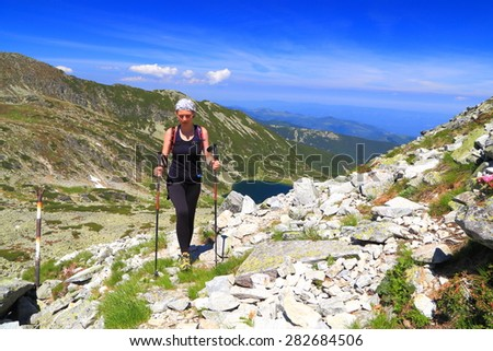 Sunny trail on the mountain and hiker walking with trekking poles  - stock photo