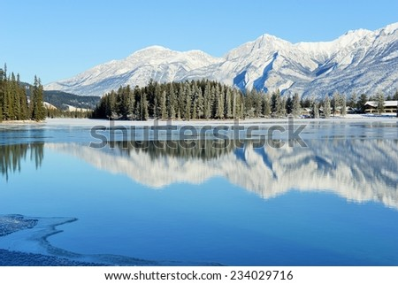 Sunny view of the reflection of mountains in freezing Lac Beauvert in Jasper National Park, Alberta, Canada - stock photo
