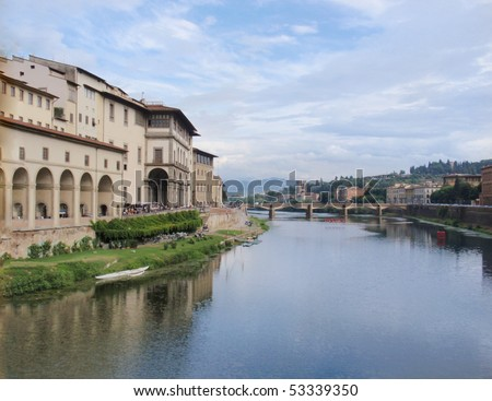 Sunny view over the River Arno in Florence in Tuscany Italy with Italys most famous medieval building the Palazzo Vecchio or the town hall - stock photo