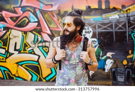 Sunny vintage photo of bearded hipster man posing on the wall,ready for deep house,punk concert.Big earphones,favorite music.Soft vintage photo,bearded hipster dj,look away - stock photo