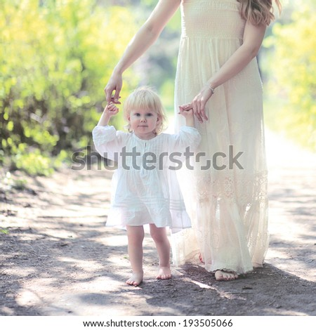 Sunny warm portrait mom and daughter walking in the forest summer day - stock photo