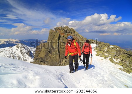 Sunny winter landscape with climbers walking on the mountain trail  - stock photo