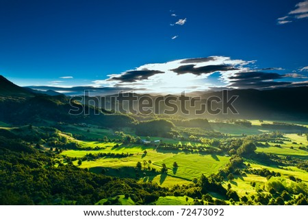 Sunrays flood farmland during sunset in amazing light - stock photo