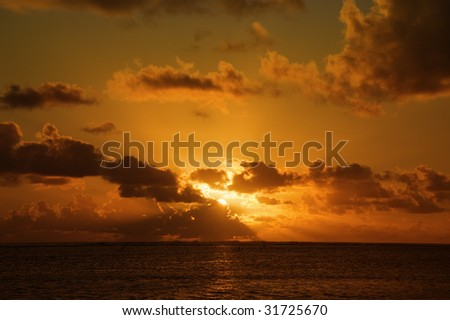 Sunrays from behind gray Clouds above South Pacific Ocean
