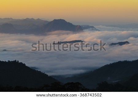 Sunrise A fog covered valley beneath a tall mountain. Thailand
