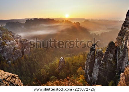 Sunrise above the misty and rocky valley in national park Saxony Switzerland - stock photo