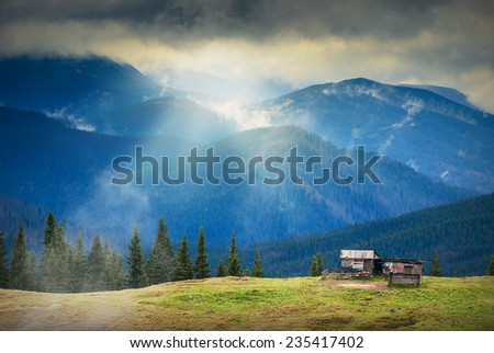 Sunrise above the nature Ukrainian wooden houses in a Carpathian mountains.  - stock photo