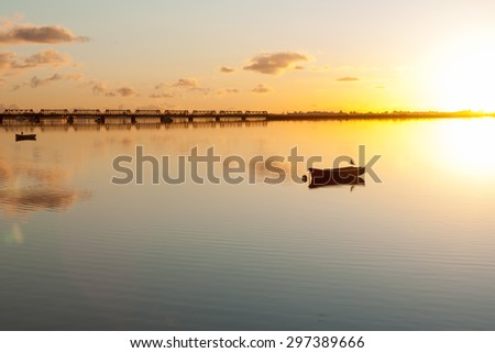 Sunrise and calmness over Tauranga Harbor. Water ripples, bird on boat and historic rail bridge on horizon.