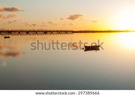 Sunrise and calmness over Tauranga Harbor. Water ripples, bird on boat and historic rail bridge on horizon. - stock photo