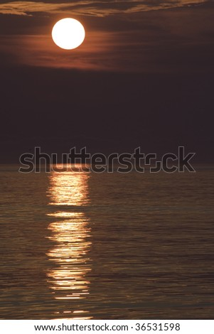 Sunrise and clouds reflected on ocean waves off the coast of North Carolina vertical - stock photo