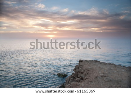 Sunrise and Dramatic sky over a clam ocean, - stock photo