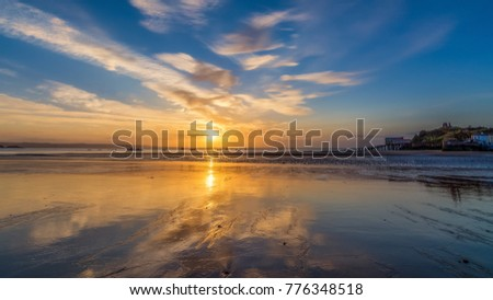 Sunrise and low tide reflections on the beach at Tenby, Pembrokeshire, Wales.