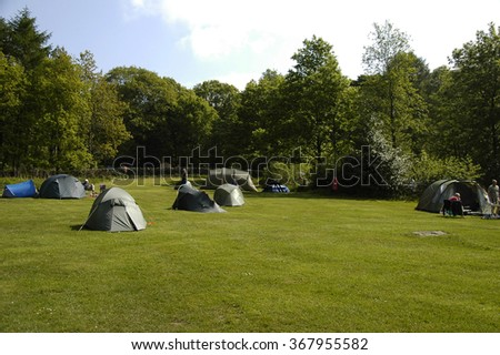 Sunrise at a campsite with several tents in Peak District National Park, England, United Kingdom - stock photo