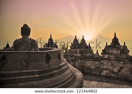 Sunrise at Borobudur temple and buddha statue - stock photo