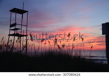 Sunrise at Kure Beach North Carolina on a warm summer morning. An empty lifeguard stand is shown as well.