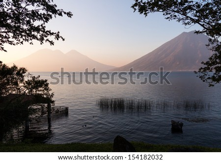 Sunrise at Lake Atitlan in Guatemala formed from volcano crater. Two small canoes are seen in the distance floating on the calm waters - stock photo