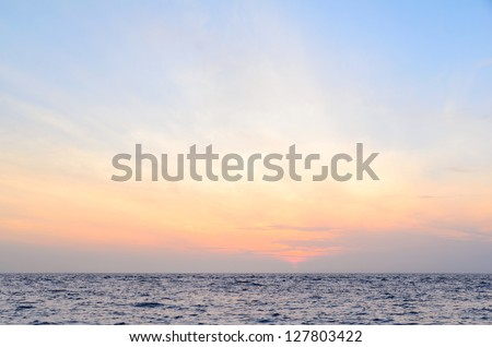 sunrise at sea on beach - stock photo