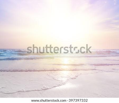 sunrise at sea on beach - stock photo