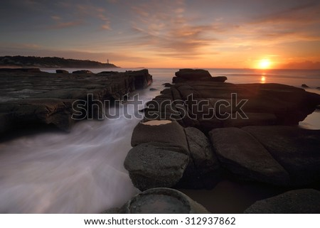 Sunrise at Soldiers Point Norah Head from the rocky reef with many chasms that the ocean has eroded over time.  Norah Head Lighthouse in the distance - stock photo