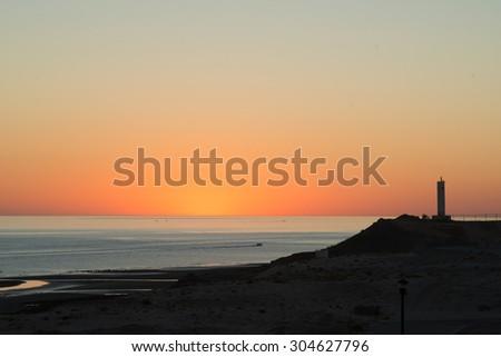 Sunrise behind the lighthouse - stock photo