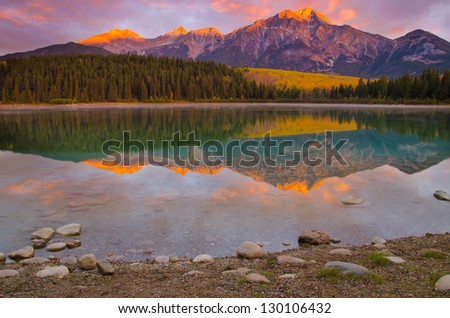 Sunrise by the an idyllic lake shore - stock photo
