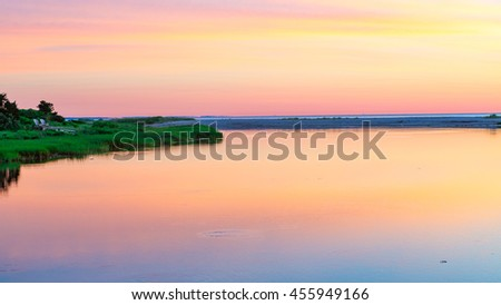 Sunrise colors fill the sky in front of the Edgartown lighthouse, Martha's Vineyard, MA - stock photo