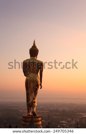 Sunrise, Golden buddha statue in Khao Noi temple, Nan Province, Thailand - stock photo
