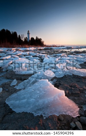 Sunrise Ice Chunks of ice washed up along the shoreline of Cana Island glow in the light of the rising sun on a frigid January morning in Door County, Wisconsin. - stock photo