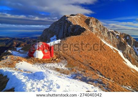 Sunrise illuminates mountain ridge and red refuge surrounded by snow patches - stock photo