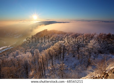 Sunrise in a mountain valley over the clouds - stock photo