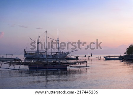 Sunrise in Bali, Indonesia. Traditional fishing boats anchor off the fishing and resort village of Pemuteran in the northwest corner of Bali, Indonesia.  - stock photo