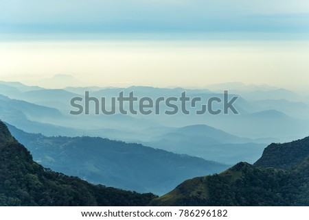 Sunrise in meadows and mountains landscape, Worlds End in Horton Plains National Park Sri Lanka.