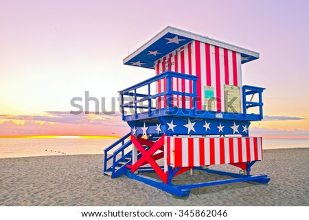 Sunrise in Miami Beach Florida, with a colorful American Flag lifeguard house in a typical Art Deco architecture, at sunrise with ocean and sky in the background.