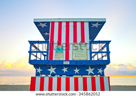 Sunrise in Miami Beach Florida, with a colorful American Flag lifeguard house in a typical Art Deco architecture, closeup at sunrise with ocean and sky in the background.