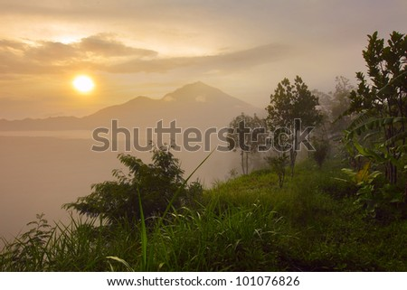 Sunrise in mountains with green tropical trees in a morning haze on the foreground - stock photo