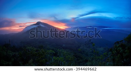 Sunrise in Sierra Nevada de Santa Marta, an isolated mountain area near to Caribbean coast. Panoramic photo with highest mountain of Colombia, Pico Cristobal Colon covered by snow in background. - stock photo