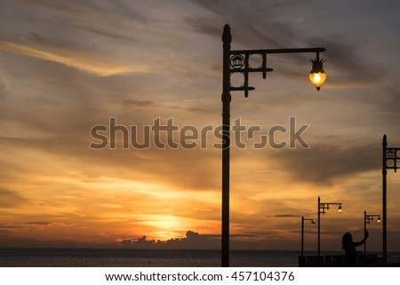 Sunrise in the morning at the sea with lamp post.