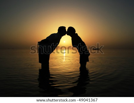 Sunrise kiss of young couple - stock photo