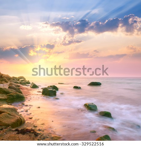 Sunrise landscape over beautiful rocky coastline in the Ocean with sunbeams - stock photo