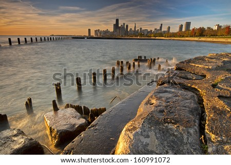 Sunrise light on a deteriorating sea wall and the Chicago skyline. - stock photo