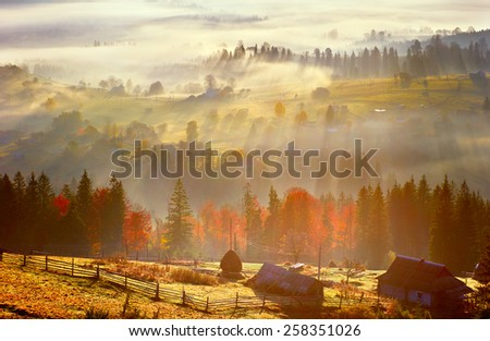 sunrise, mountain village in the fog and everything nice in yellow light - stock photo