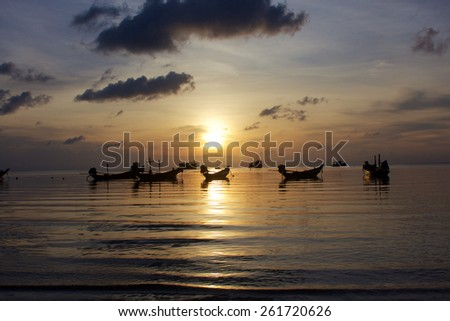 Sunrise on a calm sea with some small fishing boats in mooring - stock photo