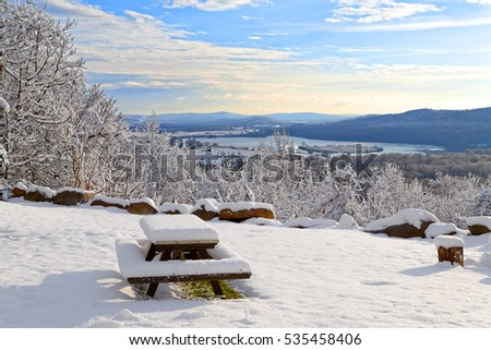 Sunrise on a snow covered mountain with a picnic table in the foreground. Lancaster County, Pennsylvania, USA.