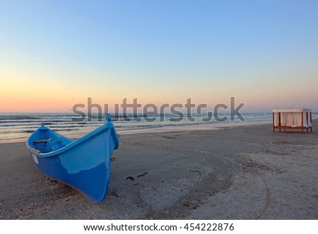 Sunrise on beach with blue boat